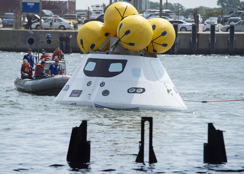 In this image provided by the U.S. Navy, sailors assigned to the amphibious transport dock ship USS Arlington practice recovering an Orion capsule Tuesday Aug. 13, 2013 into the well deck of the USS Arlington as part of NASA's first key Orion stationary recovery test at Naval Station Norfolk. NASA is partnering with the U.S. Navy to develop procedures to recover the Orion capsule and crew after splashdown. (AP Photo/U.S. Navy, Seaman Andrew Schneider)
