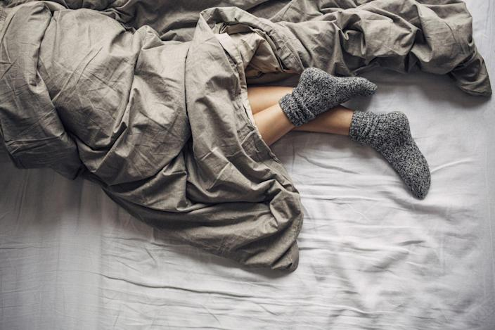 Does Wearing Socks to Bed Help You Sleep? , Feet of a woman sleeping in bed with wool socks on.