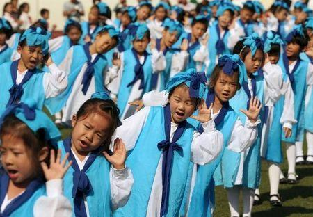 Grade-one children, wearing traditional costumes, attend an entrance ceremony in a primary school in Nantong, Jiangsu province, China, September 16, 2015. REUTERS/China Daily