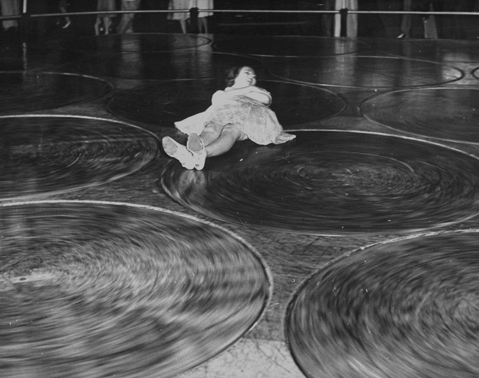 """<p>Steeplechase Park's Pavilion of Fun had many swirling rides for those with strong stomachs. The Human Roulette Wheel operated much like a Devil's Wheel, while the Human Pool Table (pictured here) challenged visitors to slide from one end of the room to another without getting thrown around by spinning platforms on the floor. </p><p><strong>RELATED:</strong> <a href=""""https://www.goodhousekeeping.com/life/g22142896/school-through-the-years/"""" rel=""""nofollow noopener"""" target=""""_blank"""" data-ylk=""""slk:Here's What School Looked Like the Year You Were Born"""" class=""""link rapid-noclick-resp"""">Here's What School Looked Like the Year You Were Born</a></p>"""