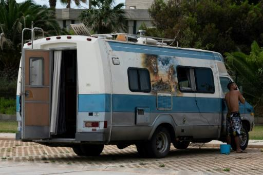 A man shaves in the rearview mirror of his well-travelled motorhome in Castellon