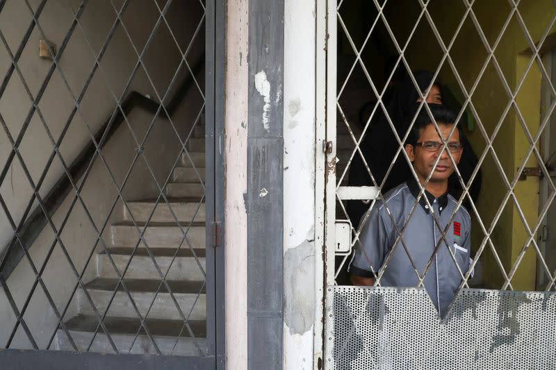 Rohingya refugee and activist Zafar Ahmad Abdul Ghani and his wife look out from their home in Kuala Lumpur