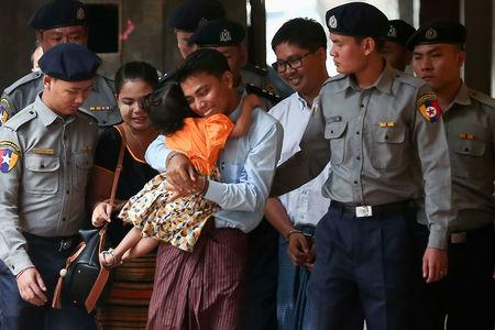 Detained Reuters journalist Kyaw Soe Oo hugs his daughter as he is escorted by police, arrives for a court hearing in Yangon, Myanmar. REUTERS/Stringer