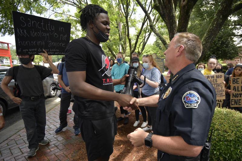 Kennesaw Chief of Police Bill Westenenberger speaks to demonstrators protesting across the street from a Confederate memorabilia store, Friday, June 5, 2020, in Kennesaw, Ga. Protests continued following the death of George Floyd, who died after being restrained by Minneapolis police officers on May 25. (AP Photo/Mike Stewart)
