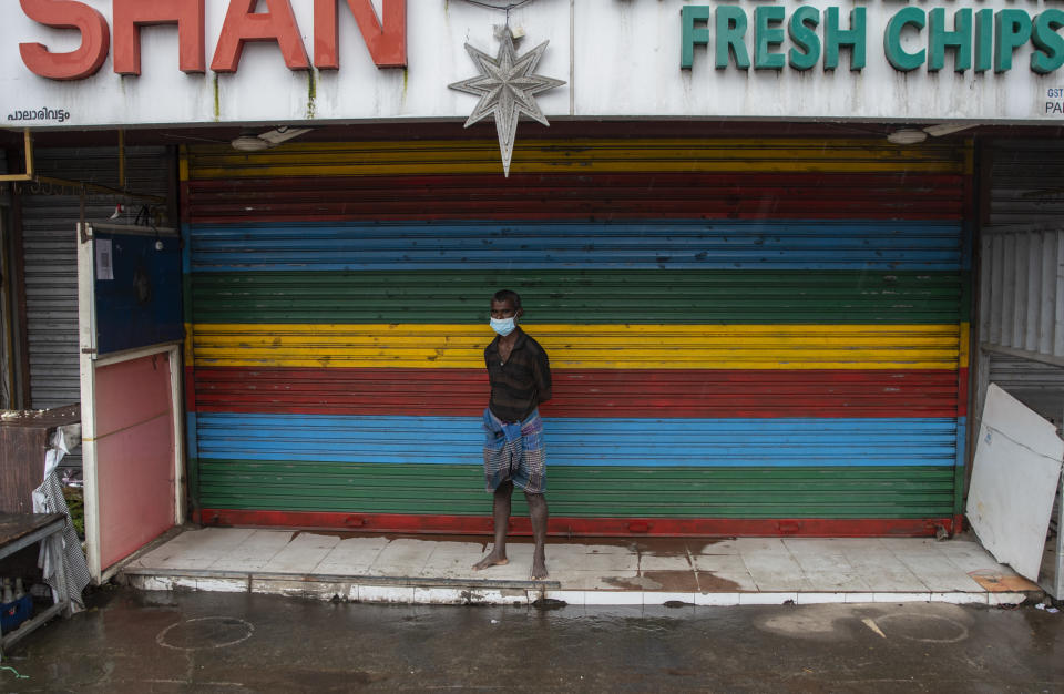 A man wearing a mask stands outside a closed shop during a nation-wide shutdown to protest against the contentious farm laws in Kochi, Kerala state, India, Monday, Sept.27, 2021. Shops remained shut and most vehicles stayed off the roads in this southern state where the ruling Left Democratic Front called for a total shutdown. (AP Photo/R S Iyer)