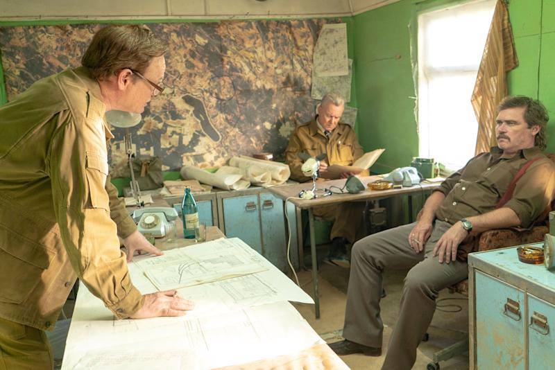 Valery Legasov (R) and lead miner Andrei Glukhov (L) talk while Boris Shcherbina sits in the background. (HBO)