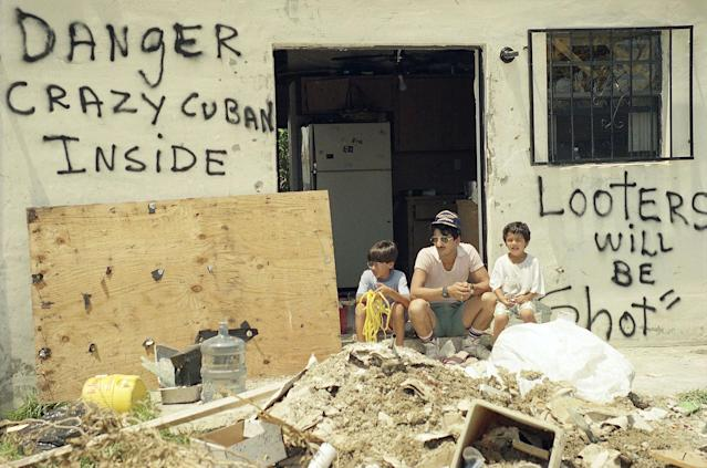 """<p>Orlando Somante, center, sits with his sons Orlando, left, and Jonathan, right, amid the rubble of their home in Cutler Ridge, with signs that warn """"Looters Will be Shot"""", and """"Danger, Crazy Cuban Inside"""", Aug. 27, 1992. Their home was one of many in South Dade County that was hit by Hurricane Andrew last Monday. (AP Photo/Gaston de Cardenas) </p>"""