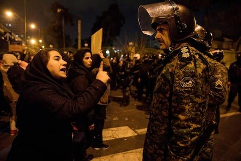 A woman attending a candlelight vigil, in memory of the victims of Ukraine International Airlines Boeing 737, talks to a policeman following the gathering in front of the Amirkabir University in Tehran - Credit: AFP