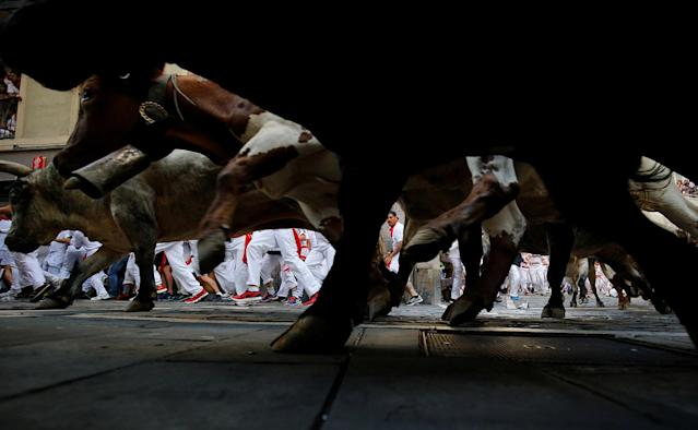 <p>A runner is seen through the legs of bulls sprinting towards the bullring during the first running of the bulls at the San Fermin festival in Pamplona, northern Spain, July 7, 2017. (Susana Vera/Reuters) </p>
