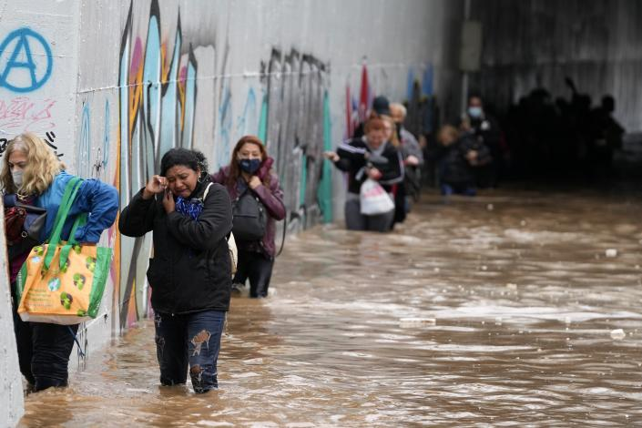 Passengers wade through high water after evacuating a bus stuck in a flooded underpass in southern Athens, Thursday, Oct. 14, 2021. Storms have been battering the Greek capital and other parts of southern Greece, causing traffic disruption and some road closures. (AP Photo/Thanassis Stavrakis)