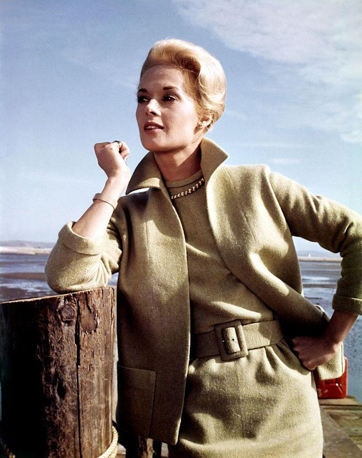 """<p>Clad in an olive green suit and pearls, Tippi Hedren poses on the set of Alfred Hitchcock's <em>The Birds</em>. The actress worked with the famous director on both the 1963 thriller and <em>Marnie </em>a year later, but recalls their professional career ending <a href=""""https://variety.com/2017/film/news/tippi-hedren-alfred-hitchcock-the-birds-sexual-harassment-1202637959/"""" rel=""""nofollow noopener"""" target=""""_blank"""" data-ylk=""""slk:after she refuted his sexual advances"""" class=""""link rapid-noclick-resp"""">after she refuted his sexual advances</a>. </p>"""