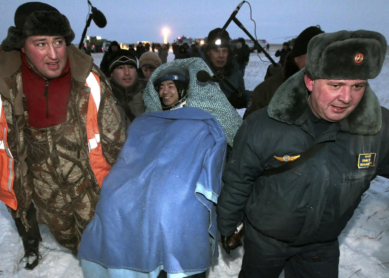 Members of the ground rescue team carry International Space Station crew member Aki Hoshide, of Japan, center, shortly after landing near the town of Arkalyk, Kazakhstan, on Monday, Nov. 19, 2012. Hoshide, NASA's Sunita Williams, and Russian astronaut Yury Malenchenko touched down in the dark, chilly expanses of central Kazakhstan onboard a Soyuz capsule Monday after a 125-day stay at the International Space Station. (AP Photo/Maxim Shipenkov, Pool)