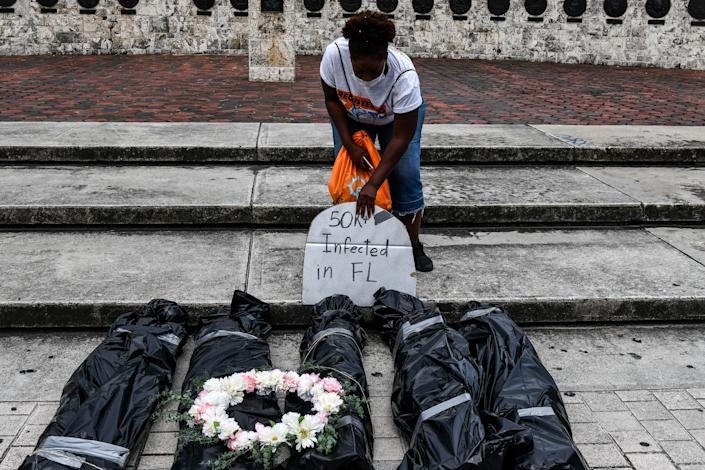 A protester sets up bags representing dead bodies during a funeral procession demonstration by the New Florida Majority (NewFM) against the reopening of Florida, in Miami, on May 27, 2020. (Chandan Khanna/AFP via Getty Images)
