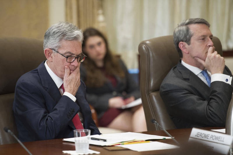 FILE- In this June 14, 2018, file photo, Federal Reserve Board Chairman Jerome Powell, left, and Vice Chair Randal Quarles listen during an open meeting in Washington. The Federal Reserve has given the OK to 32 of the 35 biggest banks in the U.S. to raise their dividends and buy back shares, judging their financial foundations sturdy enough to withstand a major economic downturn. (AP Photo/Cliff Owen, File)