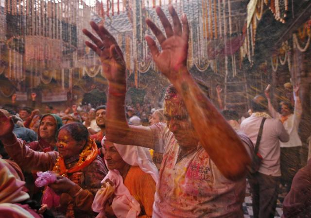 Hindu devotees react as priests (unseen) spray coloured water on them during Holi celebrations at Bankey Bihari temple in Vrindavan, in the northern Indian state of Uttar Pradesh, March 13, 2014. Holi, also known as the Festival of Colours, heralds the beginning of spring and is celebrated all over India. REUTERS/Ahmad Masood (INDIA - Tags: SOCIETY RELIGION)
