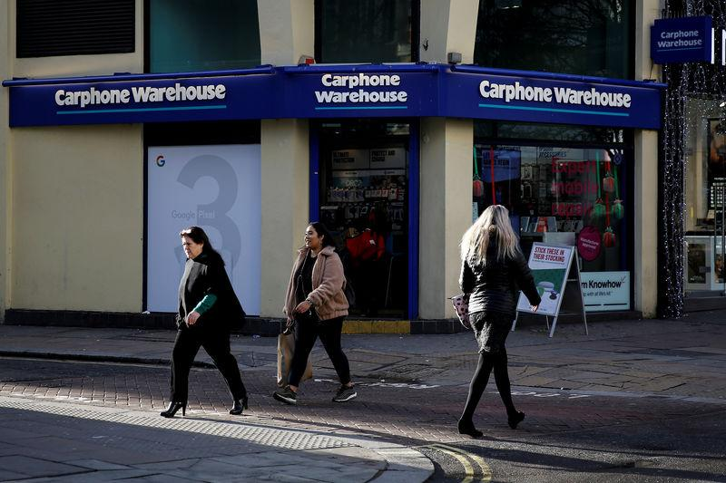 FILE PHOTO: Shoppers walk past a Carphone Warehouse store on Oxford Street in London
