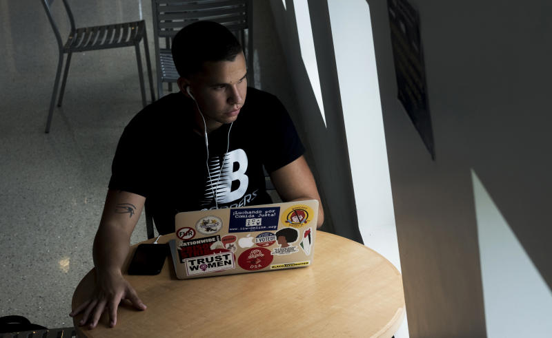 In this June 26, 2019, photo, Andy Vila, 21, speaks to callers who have phoned in to an anonymous know-your-rights hotline for immigrants who are in Miami illegally. He says his generation is more concerned with solving current problems than fighting past ideological wars. (AP Photo/Ellis Rua)