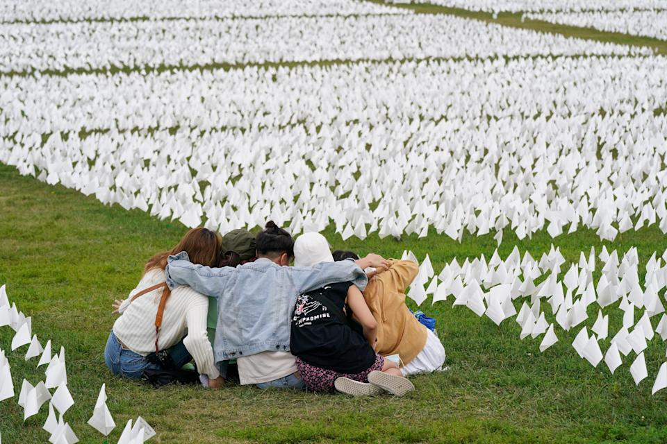 """Visitors sit among white flags that are part of artist Suzanne Brennan Firstenberg's """"In America: Remember,"""" a temporary art installation to commemorate Americans who have died of COVID-19, on the National Mall in Washington, Tuesday, Sept. 21, 2021."""