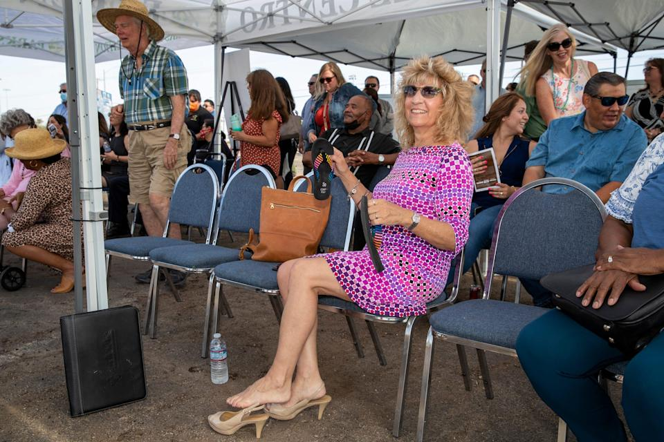 Mayor Cheryl Viegas-Walker changes out of her heels and into flats during a ground-breaking ceremony for the new El Centro Public Library in El Centro, Calif., on July 8, 2021.