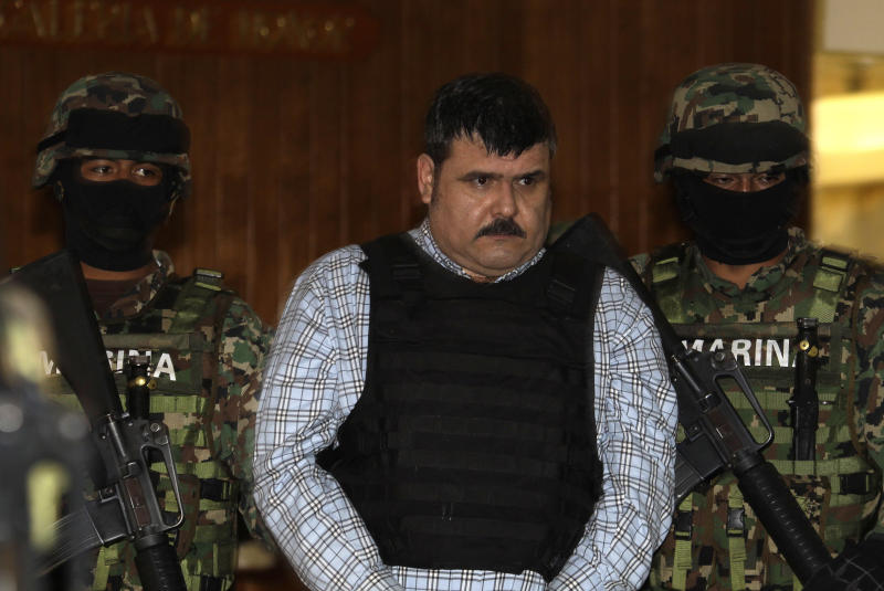 "Mexican Navy marines escort Jorge Eduardo Costilla Sanchez, aka ""El Coss,"" as he is shown to the press at the Mexican Navy's Center for Advanced Naval Studies in Mexico City,Thursday, Sept. 13, 2012. Costilla is believed to be the alleged leader of the Gulf drug cartel. One of Mexico's most-wanted men, the 41-year-old is charged in the U.S. with drug-trafficking and threatening U.S. law enforcement officials. U.S. authorities offered $5 million for information leading to his arrest. (AP Photo/Dario Lopez-Mills)"