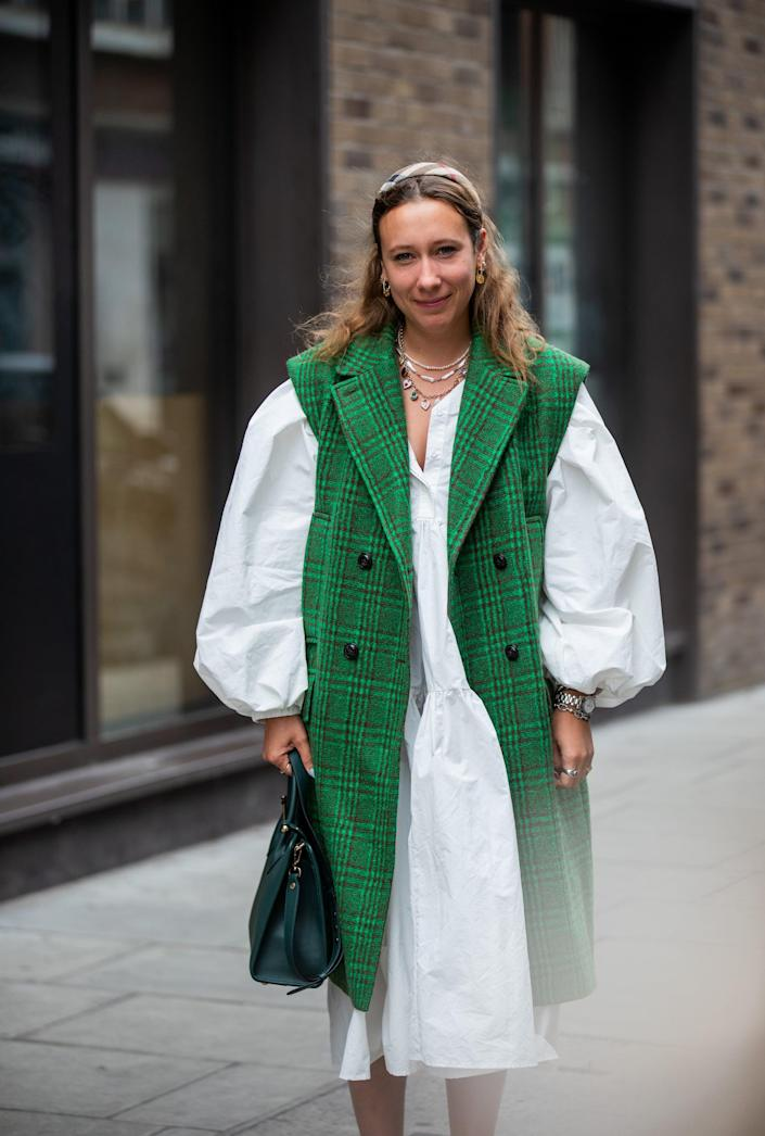 <p>This bright green vest helps to transition a pretty LWD for fall. </p>