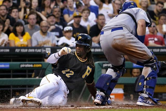 Pittsburgh Pirates' Andrew McCutchen (22) scores ahead of the tag by Los Angeles Dodgers catcher A.J. Ellis on a single by Pirates' Russell Martin during the fourth inning of a baseball game in Pittsburgh Monday, July 21, 2014. (AP Photo/Gene J. Puskar)
