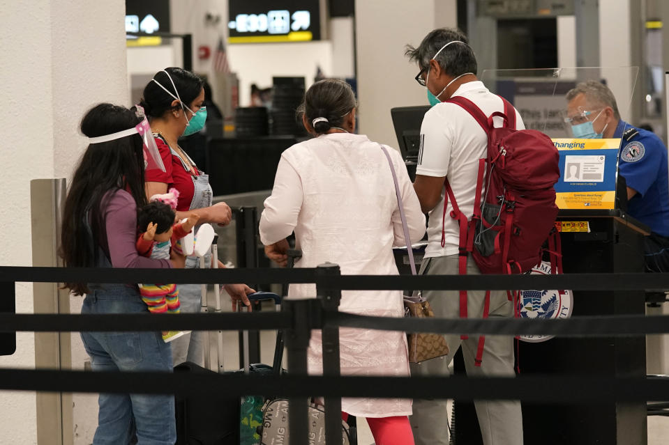 Passengers go through a security checkpoint at Miami International Airport, Wednesday, Nov. 25, 2020, in Miami. (AP Photo/Lynne Sladky)