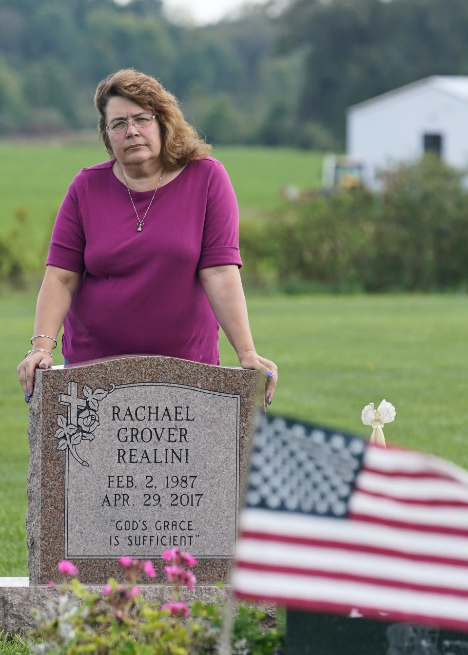 """Sharon Grover stands over the grave of her daughter, Rachael, Tuesday, Sept. 28, 2021, at Fairview Cemetery in Mesopotamia, Ohio. Grover believes her daughter started using prescription painkillers around 2013 but missed any signs of her addiction as her daughter, the oldest of five children, remained distanced. A """"bellwether trial is set to start Monday in federal court in Cleveland to determine whether retail pharmacy chains are liable for opioid crisis costs in two Ohio counties. Grover lives in Trumbull County, Ohio, which along with Lake County, have sued four retail pharmacy chains to recover """"public nuiscance"""" costs the opioid crisis continues to inflict on their communities. (AP Photo/Tony Dejak)"""
