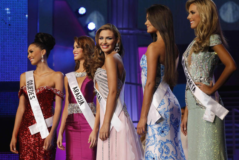 Miss Costa Oriente Migbelis Castellanos, center, competes with other contestants at the Miss Venezuela beauty pageant in Caracas, Venezuela, Thursday, Oct. 10, 2013. From left are Miss Cojedes Wi May Nava, Miss Aragua Stephani de Zorsi, Miss Costa Oriente Migbelis Castellanos, Miss Guarico Michelle Bertolini and Miss Nueva Esparta Gabriela Graf. Castellanos won the crown. (AP Photo/Ariana Cubillos)