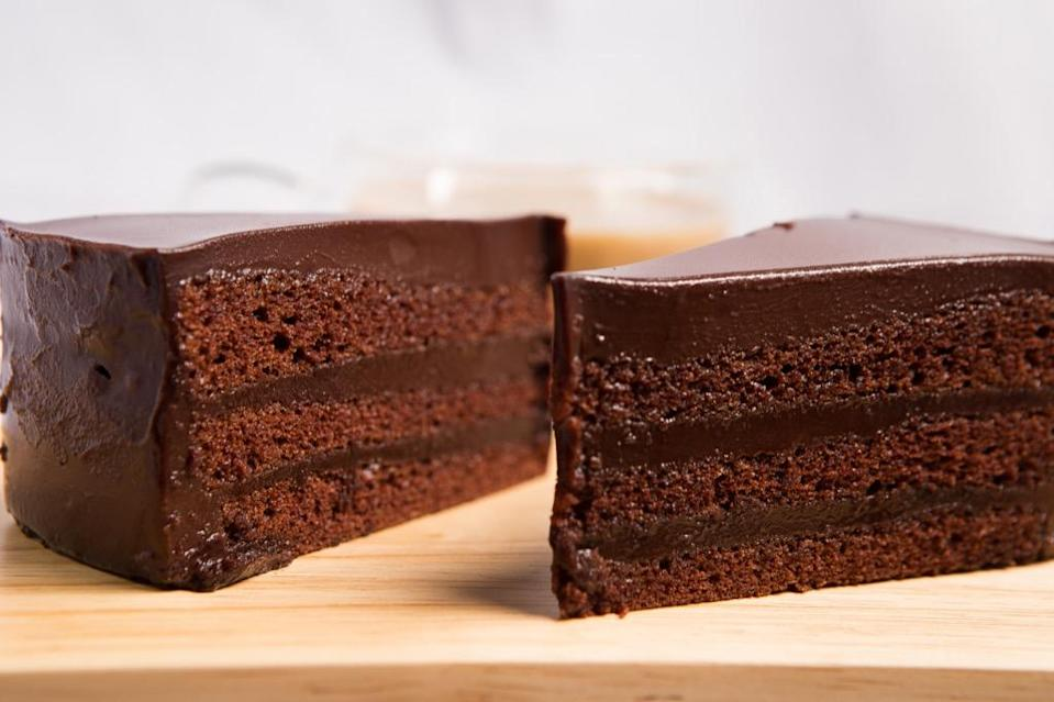 "While <a href=""https://www.npr.org/templates/story/story.php?storyId=11331541"" rel=""nofollow noopener"" target=""_blank"" data-ylk=""slk:German Chocolate Cake"" class=""link rapid-noclick-resp"">German Chocolate Cake</a> sounds like something that originally hailed from Berlin or Munich, it wasn't named after its country of origin. Instead, it was named after baker <strong>Sam German</strong>, who invented the chocolate in the cake, but not the recipe. In 1852, German, who was either American or English—not German—came up with a special kind of baking chocolate for the Baker's Chocolate Company, which named it after him, i.e. ""German's Chocolate."" When a woman in Texas used the chocolate for her cake recipe and submitted it to a Dallas newspaper more than a century later in 1957, she named the dessert ""German's Chocolate Cake."" In time, the possessive ""'s"" was dropped and it became German Chocolate Cake."