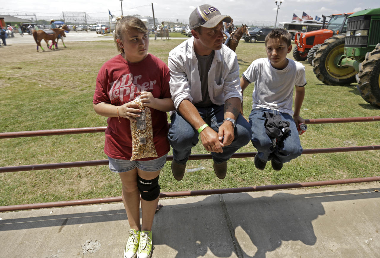 "Inmate Jonah Maynard sits with his niece Raylin Maynard, 15, and Jacob Campbell, 12, at the Angola Prison Rodeo in Angola, La., Saturday, April 26, 2014. Louisiana's most violent criminals, many serving life sentences for murder, are the stars of the Angola Prison Rodeo, the nation's longest-running prison rodeo that this year celebrates 50 years. The event has grown from a small ""fun"" event for prisoners into big business, with proceeds going into the Louisiana State Penitentiary Inmate Welfare Fund for inmate education and recreational supplies. (AP Photo/Gerald Herbert)"