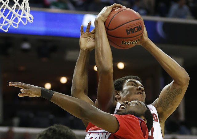 Dayton guard Khari Price (0) and Stanford forward Josh Huestis (24) vie for a loose ball during the first half in a regional semifinal game at the NCAA college basketball tournament, Thursday, March 27, 2014, in Memphis, Tenn. (AP Photo/John Bazemore)