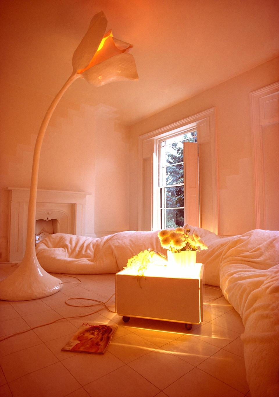 Tall flower-shaped floor lamp and serpentine cushion sofa in Sixties living room designed by Max Clendinning - Alamy