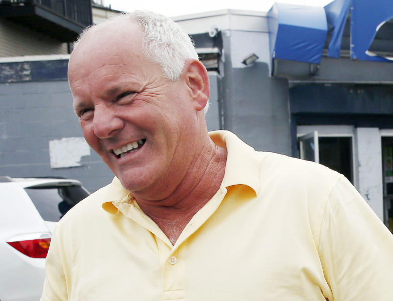 "FILE - In this June 6, 2013 photo, Stephen Rakes smiles outside the liquor store he once owned in the South Boston neighborhood of Boston. Rakes, who said he had been extorted by James ""Whitey"" Bulger and hoped to testify at his trial, was given iced coffee laced with cyanide that killed him, authorities said Friday, Aug. 2, 2013, and that 69-year-old William Camuti, of Sudbury, is charged with attempted murder in his death. Rakes' body was found July 17 in the woods in suburban Boston the day after he learned he would not be called to testify. (AP Photo/Michael Dwyer, File)"