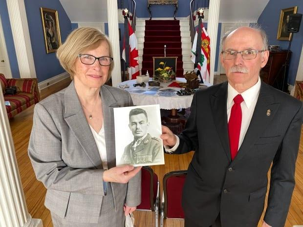 Kathy Large and historian Ian Scott host a remembrance ceremony at Fanningbank to mark 100 years since first radio broadcast on P.E.I. Large holds a photo of her grandfather, Keith Rogers, who was part of P.E.I.'s first radio broadcast. (John Robertson/CBC - image credit)