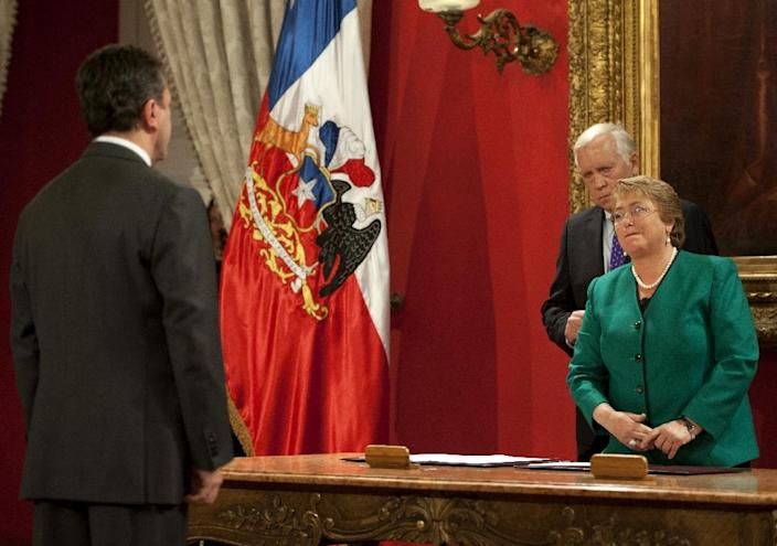 Chilean President Michelle Bachelet stands next to her Minister of Interior, Jorge Burgos (R) and Minister of Defense, Jose Antonio Gomez (L) during the presentation of the new Cabinet at La Moneda presidential palace on May 11, 2015 (AFP Photo/Vladimir Rodas)