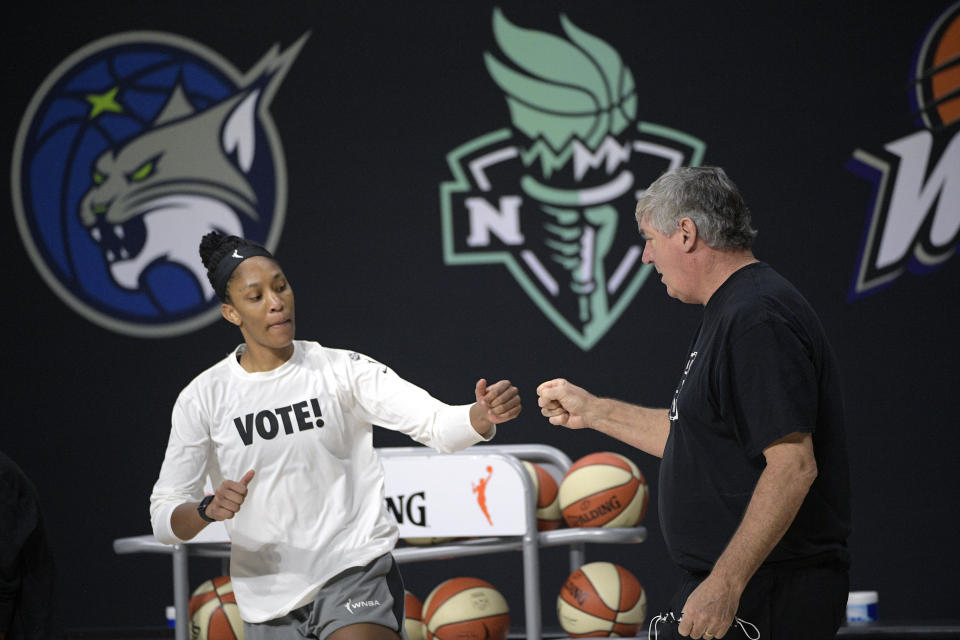 """A'ja Wilson in a white """"VOTE!"""" T-shirts giving a fist bump to Bill Laimbeer."""