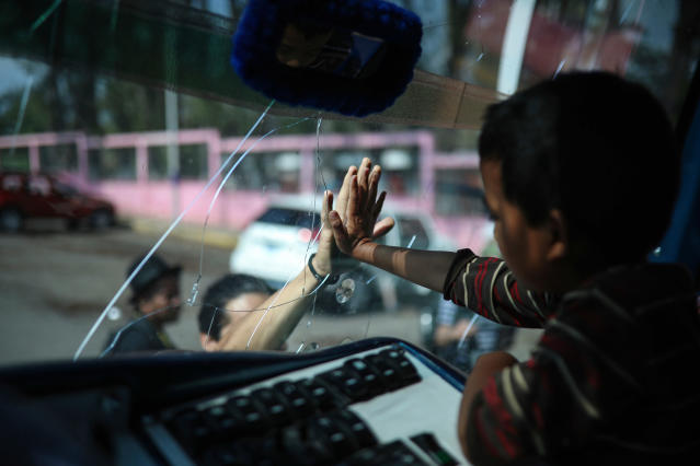 "<p>A boy says goodbye to a friend through the windshield of a bus that will carry him to Mexico City from the sports club where Central American migrants traveling with the annual ""Stations of the Cross"" caravan had been camping out in Matias Romero, Oaxaca State, Mexico, Thursday, April 5, 2018. (Photo: Felix Marquez/AP) </p>"