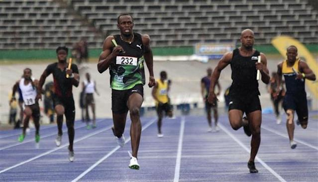Jamaican runners Usain Bolt (232) of the Racers Track Club races ahead of Asafa Powell (2nd R) of the MVP Track Club in the men's 4x100m relay at the Utech Classic in Kingston April 14, 2012. Bolt finished first and Powell second. Picture taken April 14, 2012.