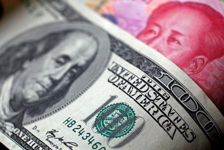 FILE PHOTO: Photo of a Chinese 100 yuan banknote being placed under a $100 banknote in this photo illustration taken in Beijing