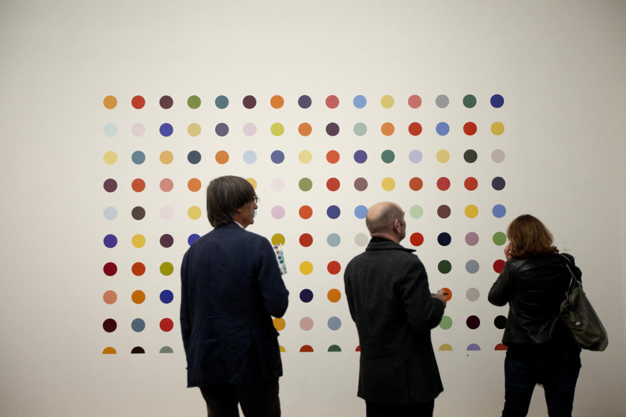 "People look at British artist Damien Hirst's 1986 piece ""Spot Painting"", household gloss on board, during a media preview of the first substantial show of his work in the UK at the Tate Modern gallery in London, Monday, April 2, 2012. The exhibition, timed for the culmination of the Cultural Olympiad and due to open to the public on Wednesday, showcases over 70 of Hirst's works since he first came to public attention in 1988. (AP Photo/Matt Dunham)"