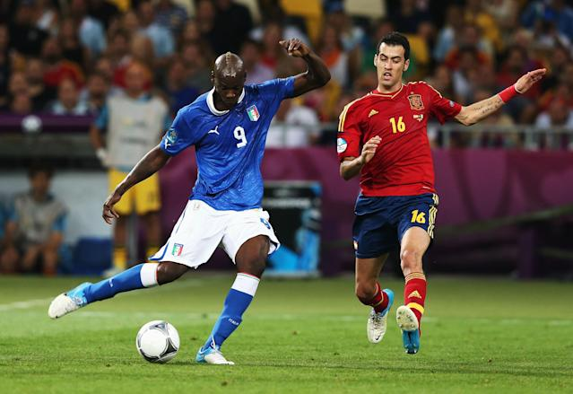 KIEV, UKRAINE - JULY 01: Mario Balotelli (L) of Italy shoots at goal past Sergio Busquets of Spain during the UEFA EURO 2012 final match between Spain and Italy at the Olympic Stadium on July 1, 2012 in Kiev, Ukraine. (Photo by Alex Grimm/Getty Images)