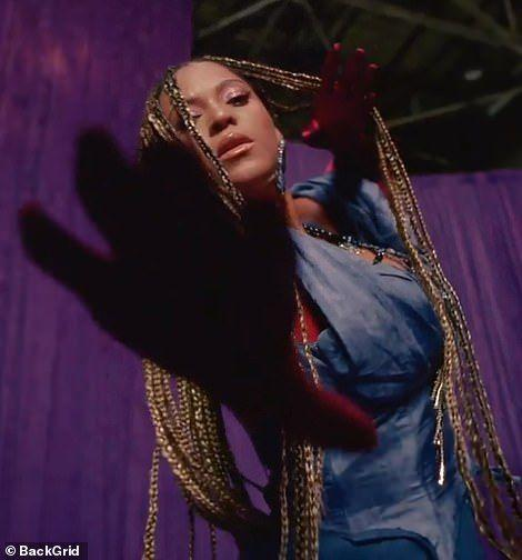 <p>Beyoncé wears a fitted blue denim top and larger-than-life jeans by Michaela Stark. </p>