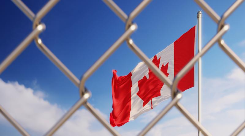 Fence in front of Canadian flag. Illegal immigration concept. Horizontal composition with copy space. (Photo: MicroStockHub via Getty Images)