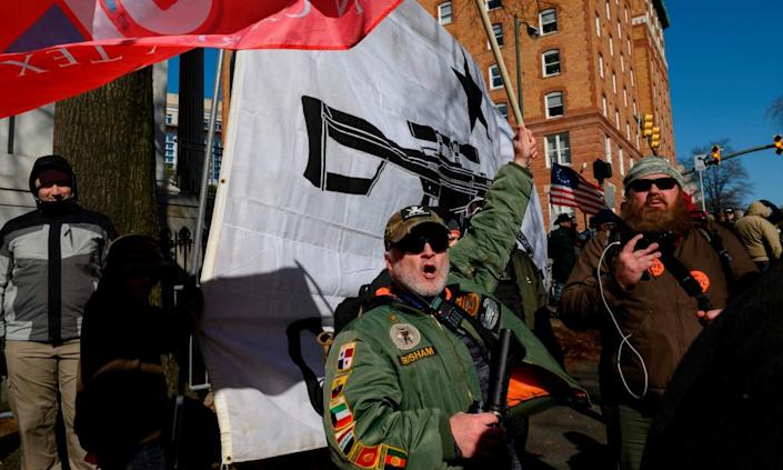 A pro-gun protester, holding an automatic rifle, waves a flag outside the Virginia State Capitol in Richmond, in January.