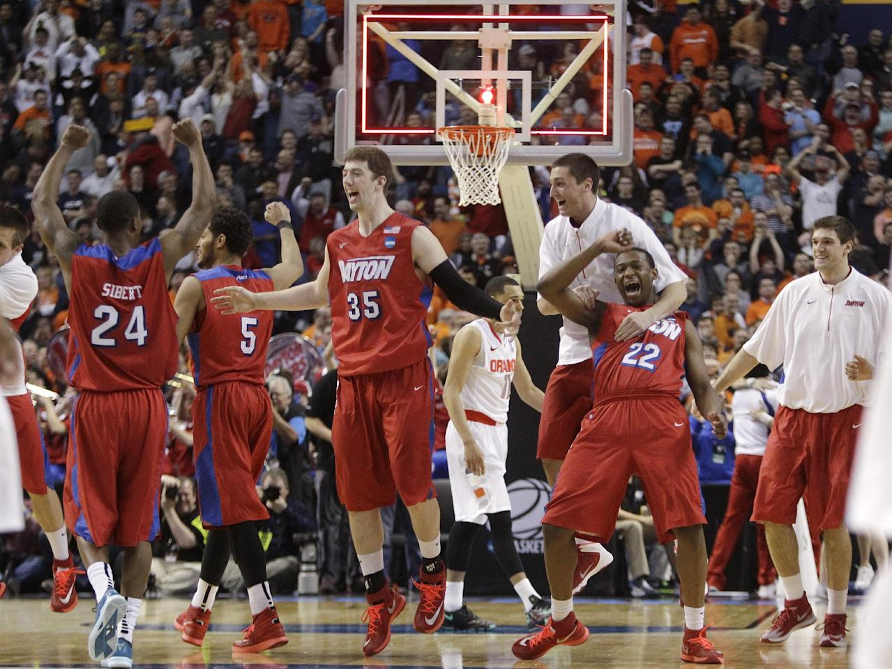 Dayton's Jordan Sibert (24), Matt Kavanaugh (35) and Kendall Pollard (22) celebrate after a third-round game against Syracuse in the NCAA men's college basketball tournament in Buffalo, N.Y., Saturday, March 22, 2014. Dayton won 55-53. (AP Photo/Bill Wippert)