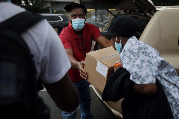 PHOTO: Guibert Tercino hands out boxes of food to people outside a comfort station run by the Boston Public Health Commission on Massachusetts Ave. in Boston, Sept. 10, 2020. (Craig F. Walker/The Boston Globe via Getty Images)