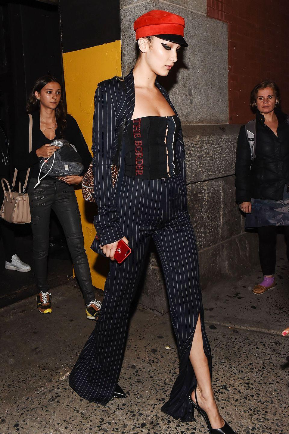 <p>In a corset top with a navy pinstriped suit, Alexander Wang heels and a red newsboy hat while leaving the Marc Jacobs show in New York City.</p>