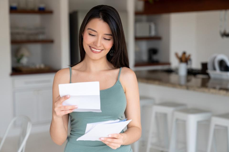 happy young woman reading letter