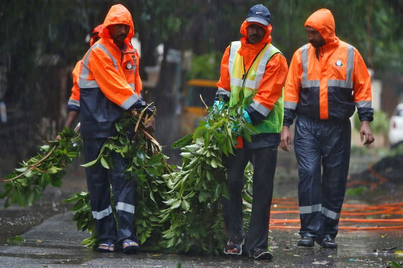Municipal workers remove fallen tree branches from a road during rains before Cyclone Nivar's landfall, in Chennai